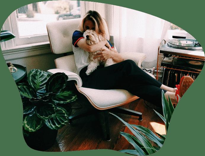 Frau in Wohnung auf dem Sessel mit Hund auf dem Schoss